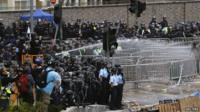 Riot police use a water cannon to disperse protesters
