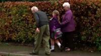 Schoolgirl walking with grandparents
