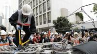 Workers remove a barricade at an area blocked by pro-democracy protesters