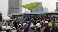 A worker holds an umbrella near the government headquarters
