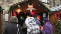 Pensioners shopping at a Winchester Christmas market stall selling decorations in the shape of stars