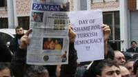 Protesters holding aloft the Zaman newspaper, the editor of which has been arrested, and a sign reading 'Day of shame for Turkish democracy!!!'