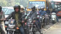 Motorbikes and cars wait at traffic lights in India's capital city Delhi