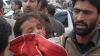 Man carrying small girl injured in Taliban attack on Pakistan school