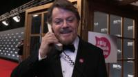 Eddie Izzard standing outside a phone box on the telephone