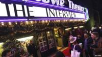 "Fans line up at the Silent Movie Theatre for a midnight screening of ""The Interview"" in Los Angeles"