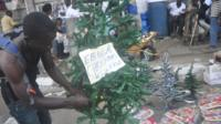 A man arranges a Christmas tree at a shop in Monrovia, Liberia, on 24 December