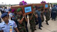 Indonesian military carry the caskets containing the bodies of two passengers