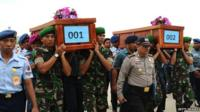 Indonesian soldiers carry coffins containing victims of the AirAsia flight QZ8501 crash