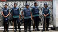 Members of the Bangladeshi police forces stand guard