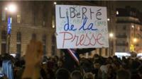 """A participant holds a placard with the words; """"Freedom of the Press"""", as thousands gather for a candle light vigil on Place de la Republique in central Paris hours after the attack by two gunmen on the """"Charly Hebdo"""" headquarters in Paris, France, 07 January 2015"""