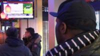 Parisians watch the siege unfold on a TV screen in a cafe