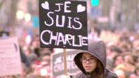 "Protester in Paris holds a banner displaying ""Je Suis Charlie"" (I am Charlie)"