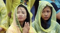 Young Filipino women pray during the visit of Pope Francis