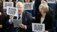 Theresa May and Eric Pickles holding Je Suis Juif signs