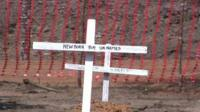 A white cross marking a grave with 'New born boy unnamed' written on it