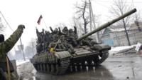 Armed pro-Russian rebels ride a tank in downtown Donetsk