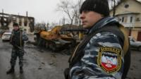 "Members of the police of the separatist self-proclaimed Donetsk People""s Republic gather near a burnt-out armoured vehicle in Vuhlehirsk, Donetsk region"
