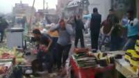 Iraqis caught up in the aftermath of an explosion outside a cinema in Baghdad