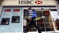 A pedestrian passes a branch of HSBC bank in London