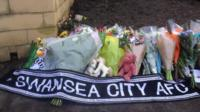 Tributes to the men from the Swansea area were laid at the scene