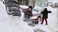 Couple shovelling snow from around car
