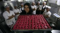 Pooja Dhingra holding a tray of macarons in front of some members of staff