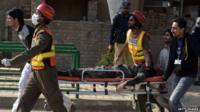Pakistani volunteers move an injured worshipper near a Shiite Muslim mosque after an attack there by Taliban militants in Peshawar on 13 February 2015