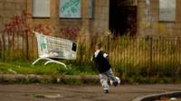 Child playing football in deprived area
