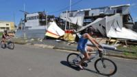 Residents cycle past a cyclone damaged business in the northern Queensland town of Rockhampton