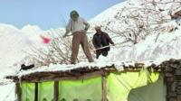 Residents shovel snow off of a roof