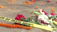 Flowers laid at sight of killing of blogger Avijit Roy with police tape saying 'Crime scene do not cross'