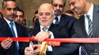 Iraq's Prime Minister Haider al-Abadi cutting a red ribbon at the re-opening of Iraq's National Museum in Baghdad