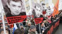 Protesters hold up pictures in a protest in Moscow