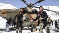 Workers load relief goods on an Army helicopter to be distributed to avalanche hit areas, in Panjshir province, Afghanistan