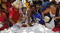 People take cake baked for an event marking the city's 450th birthday in Rio de Janeiro, Brazil