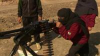 A woman taking aim down the sights of a heavy machine gun