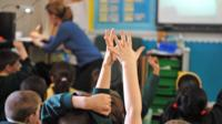 School pupils raise their hands in the classroom