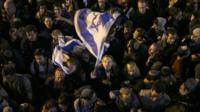Woman in crowd waving an Israeli flag