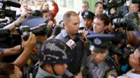 New Zealand citizen Philip Blackwood (C), escorted by Myanmar policemen as he comes out from court after being sentenced two and a half years in prison