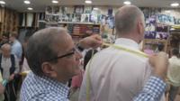 Sam tailor measuring man in shop