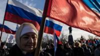 Crimeans wave Russian flags as they celebrate the first anniversary of the referendum