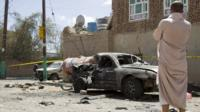 Man stands by vehicle destroyed in suicide attack