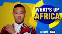 Satirist Ikenna Azuike in front of 'What's up Africa' logo