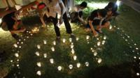 "Members of the public light candles to form the acronym ""R. I. P."" at a local community club in Singapore"