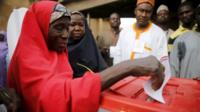 A woman casts her vote at a polling unit in Daura, northwest Nigeria