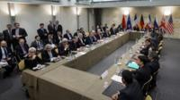 Officials await the opening of a plenary session on Iran nuclear talks