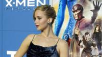 Actress Jennifer Lawrence who plays Mystique standing in front of an X-Men film poster