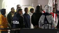Italian authorities guide migrants who survived ship sinking at Catania's port in Sicily