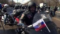 Bikers, one with a Russian flag on his bike